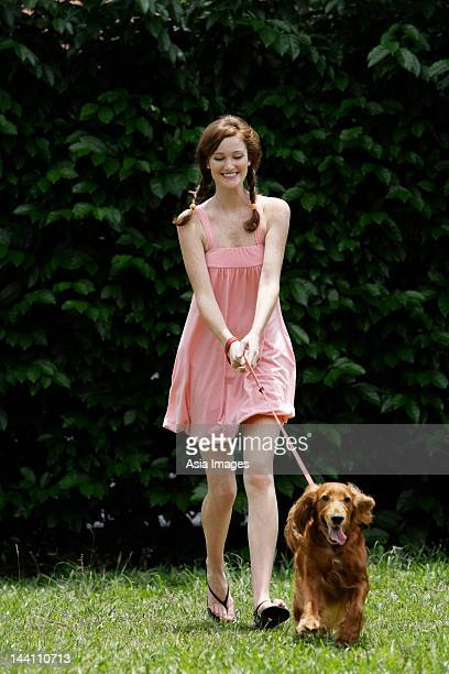Young woman being pulled by dog on leash
