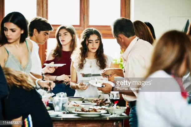 Young woman being served food during multigenerational family dinner party