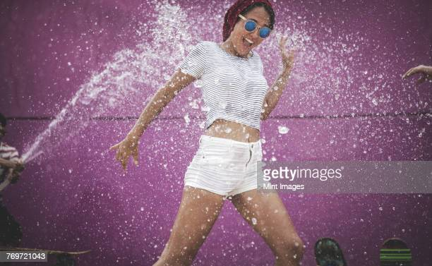 a young woman being sprayed with water. - purple pants stock pictures, royalty-free photos & images