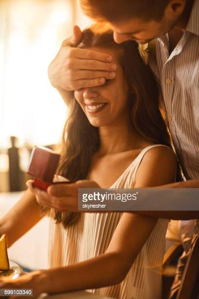 Young woman being surprised by her boyfriend with engagement ring.