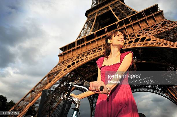 Jeune femme avec vélo-dessous de la Tour Eiffel à Paris, France