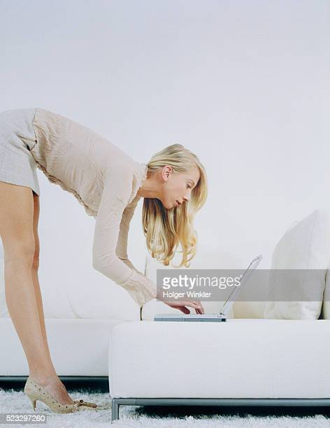 young woman bending forward sofa and using laptop - high heels short skirts stock pictures, royalty-free photos & images
