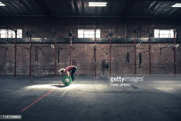 young woman bending forward to lift barbell in gym - dansstudio stock pictures, royalty-free photos & images