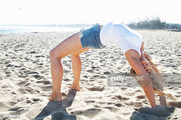 Young woman bending over backwards on beach, Melbourne, Victoria, Australia