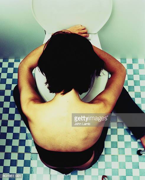Young woman bending over toilet bowl, close-up, overhead view