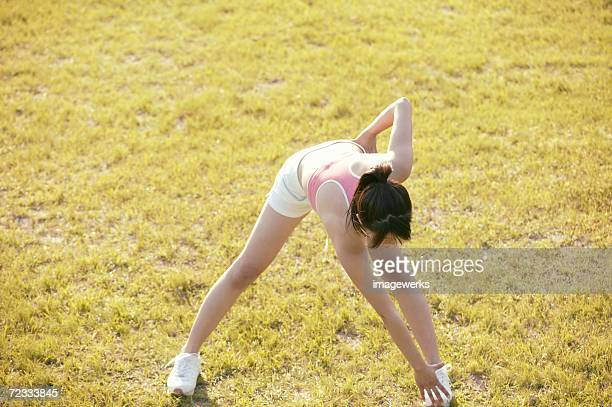 a young woman bends and touches her feet while she exercises amidst grassland - frau gespreizte beine stock-fotos und bilder