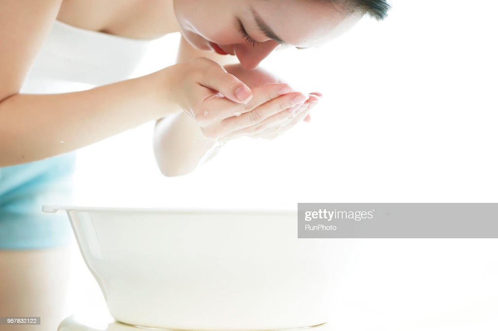 Young woman bent over bowl, washing face : ストックフォト
