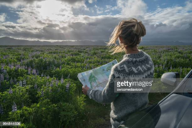 Young woman beside car looking at map, road trip concept vacations