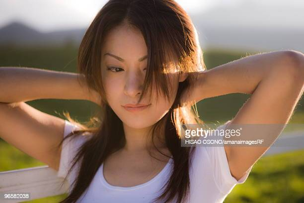 young woman beside pasture, tochigi prefecture, japan - 髪に手をやる ストックフォトと画像