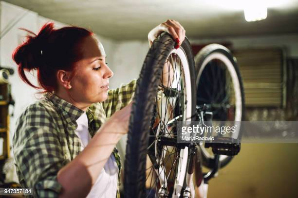 young woman bicycle mechanic is repairing a bike in the workshop - overtime sport stock pictures, royalty-free photos & images