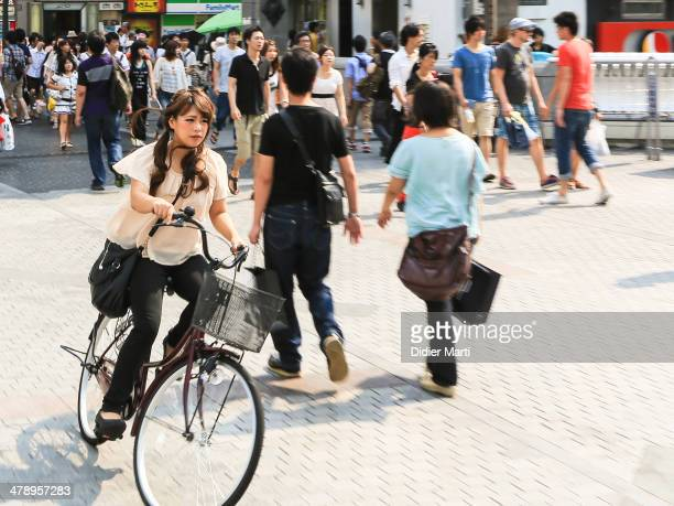 Young woman bicycling in the streets of Tokyo in Japan