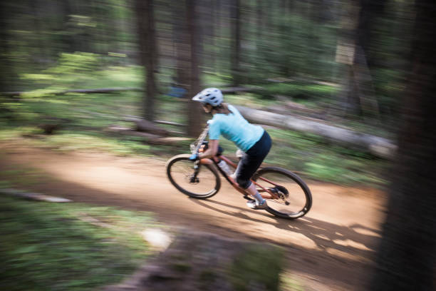A young woman bikes on a trail in a forest in Oregon's forest.
