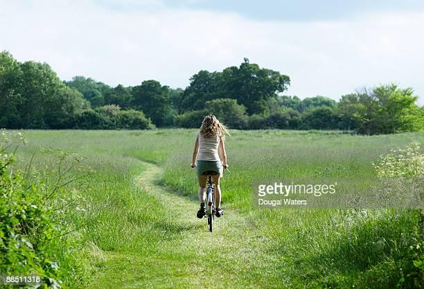 Young woman biking through countryside meadow.