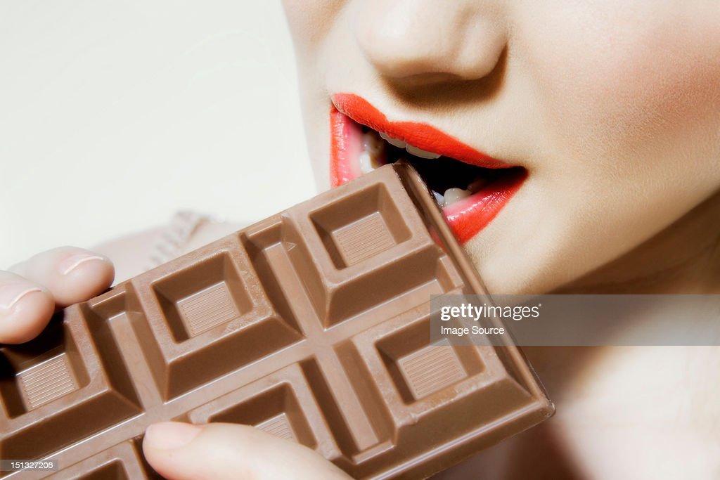 Young woman biting chocolate, close up : Stock Photo