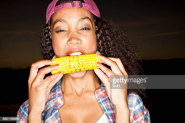 young woman biting corn on the cob looking at camera - corn on the cob stock pictures, royalty-free photos & images