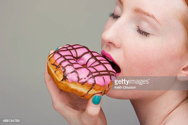 Young woman biting donut