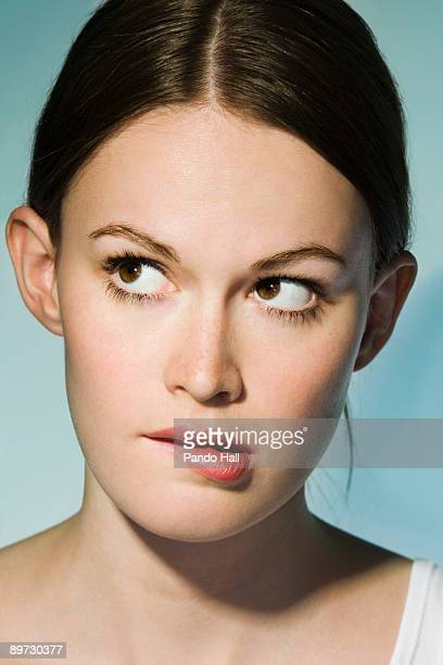 Young woman biting her lip, looking up, clsoe-up