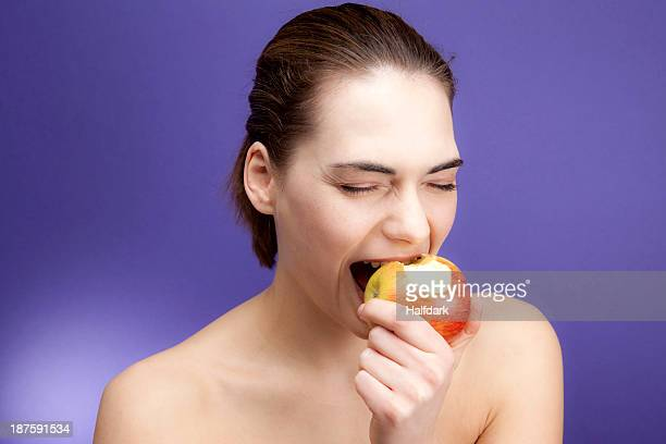 A young woman biting into an apple greedily
