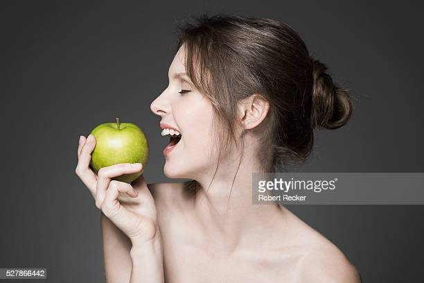Young woman biting into green apple