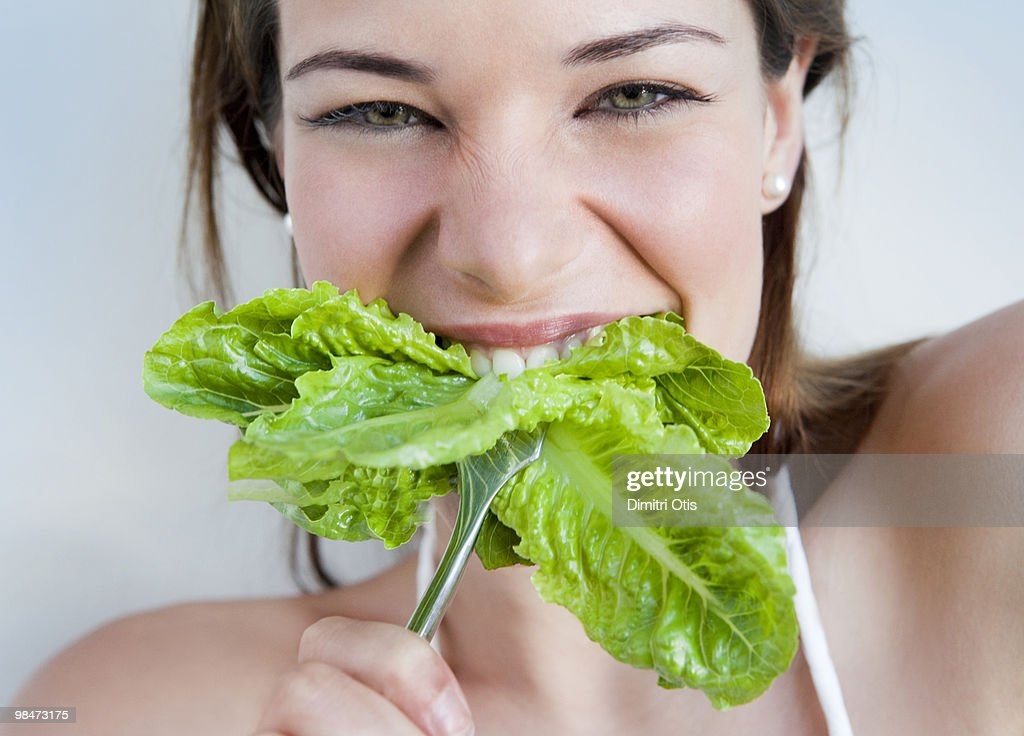 Young woman biting into lettuce : Stock Photo