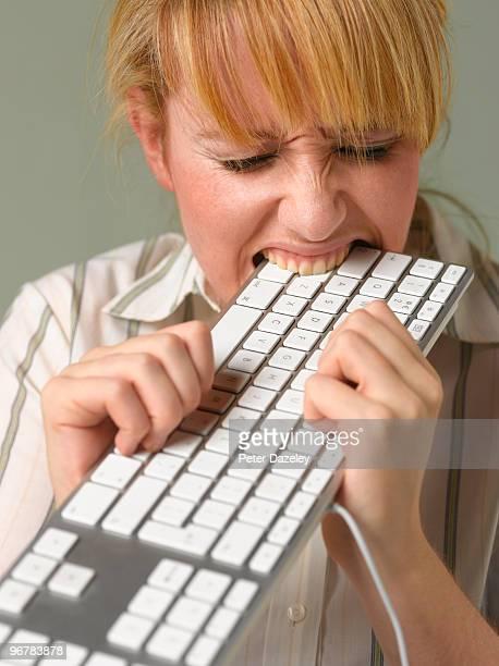 Young woman biting keyboard