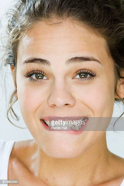 Young woman biting lip and smiling, portrait