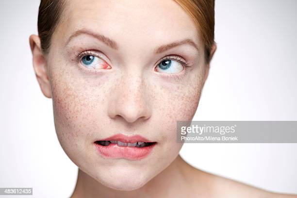 young woman biting lips - biting lip stock pictures, royalty-free photos & images
