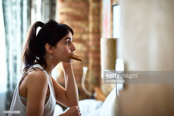 Young woman biting piece of toast and checking herself in mirror