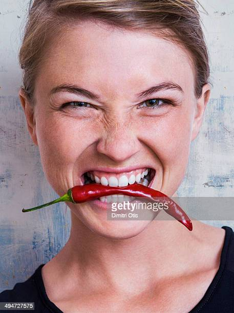 Young woman biting red hot chilli