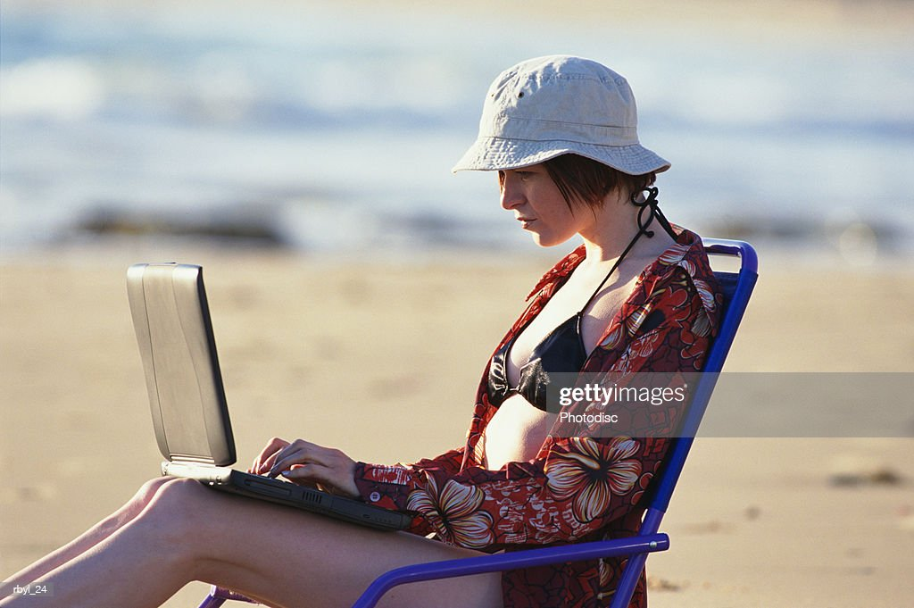 young woman black bikini flowered shirt tan hat sits in chair laptop computer the ocean sand behind : Foto de stock