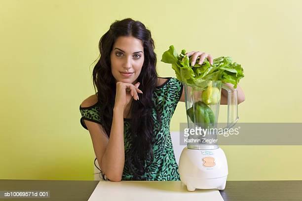 Young woman blending vegetables, indoors, portrait