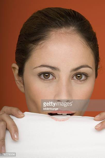 young woman blotting lipstick on tissue