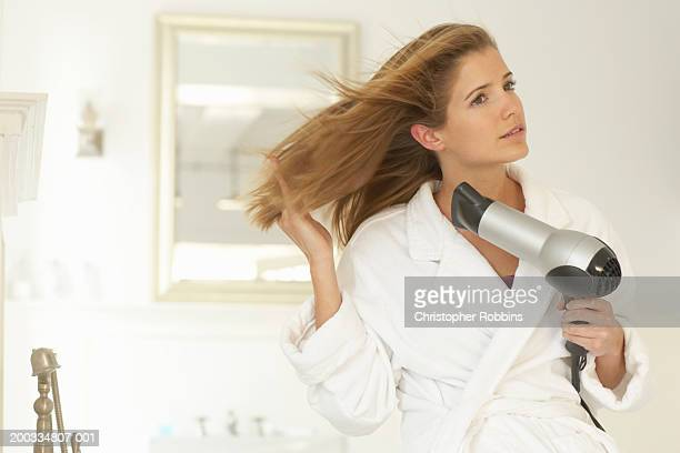 young woman blowdrying hair, wearing dressing gown - blow drying hair stock pictures, royalty-free photos & images