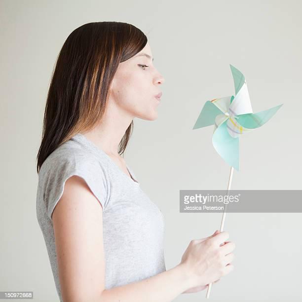 young woman blowing at paper fan - sólo con adultos fotografías e imágenes de stock
