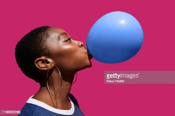 young woman blowing balloon against pink background - lifestyle stock pictures, royalty-free photos & images