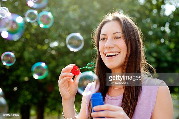 Young woman blowing bubbles and laughing.