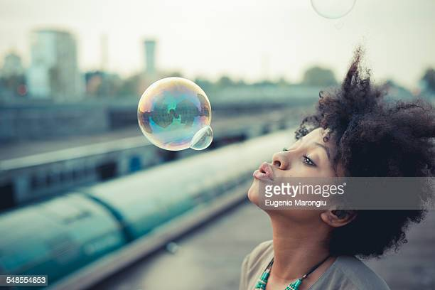 Young woman blowing bubbles in city industrial area
