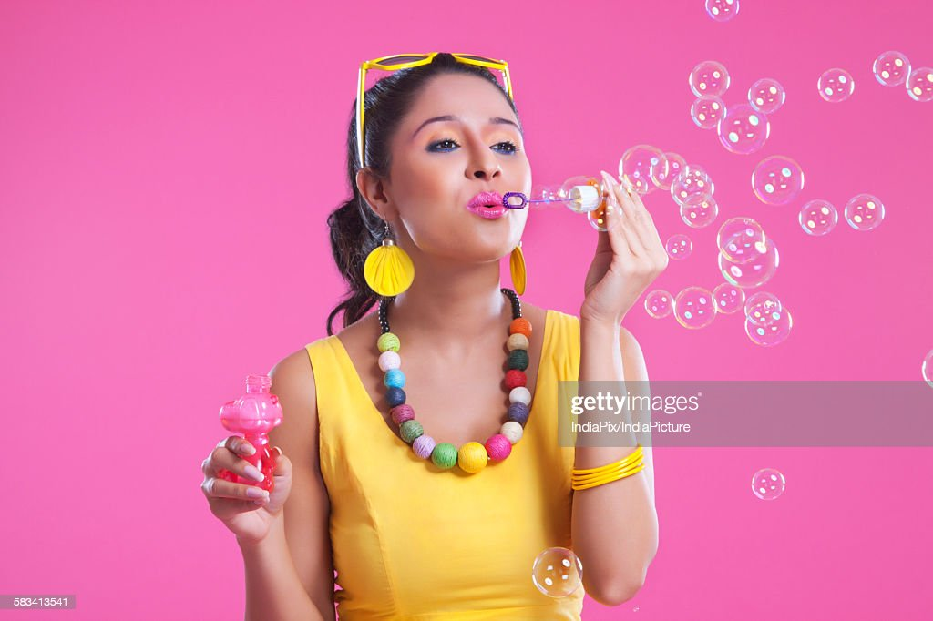 Young woman blowing bubbles : Stock Photo