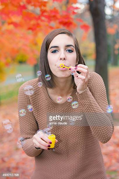 Young woman blowing bubbles under a maple tree
