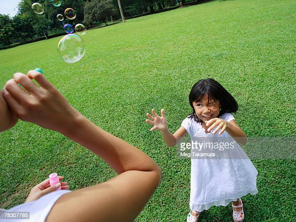 Young woman blowing bubbles with her daughter looking at her