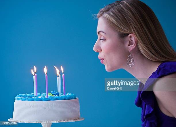 young woman blowing candles on birthday cake, studio shot - soplar fotografías e imágenes de stock
