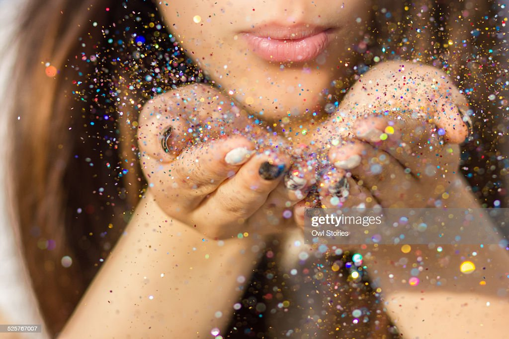 Young woman blowing colorful glitter in the air : Stock Photo