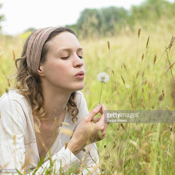 Young woman blowing dandelion.