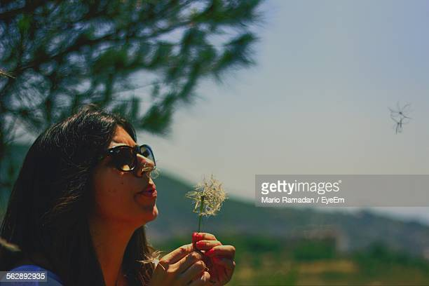 Young Woman Blowing Dandelion Seed While Standing In Park