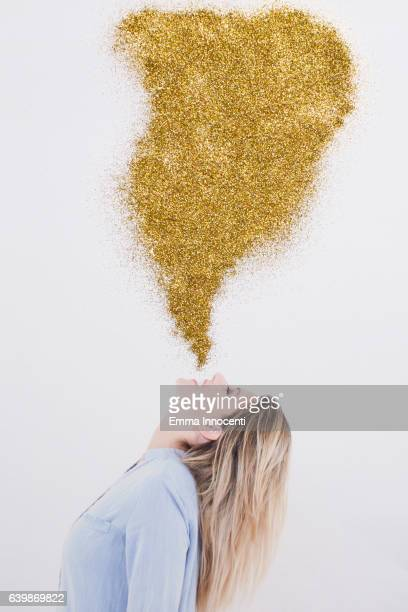 Young woman blowing gold dust into the air