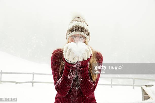 Young woman blowing handful of powder snow