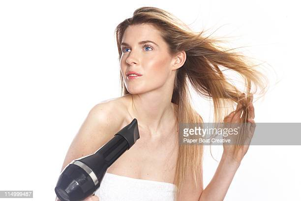 young woman blowing her hair dry