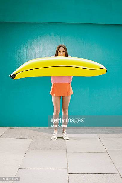 Young woman blowing inflatable banana