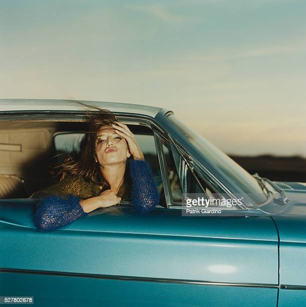 Young Woman Blowing Kiss from Vintage Car