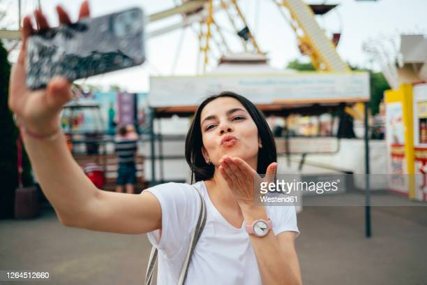 young woman blowing kiss while taking selfie in amusement park - one young woman only stock pictures, royalty-free photos & images
